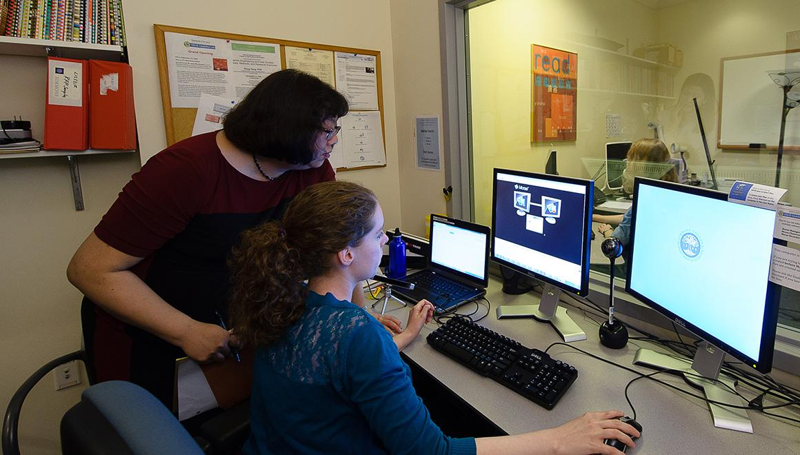 Professor and student working on a computer