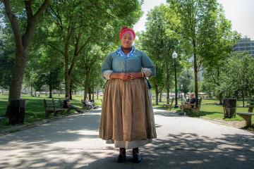 Cheyney McKnight standing in the Boston Common dressed as an enslaved woman.