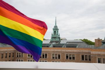 Pride flag waving with Simmons cupola in the background.