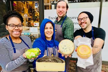Hannah Morrow holding cheeses with her coworkers.