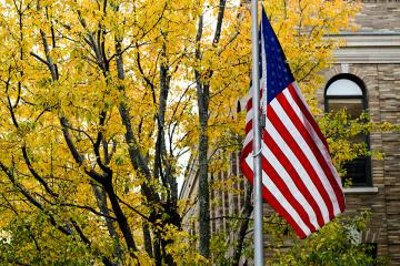 US flag in front of the Simmons University Main College Building in the fall.
