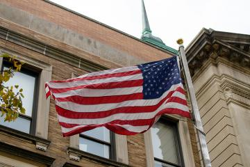 The American flag flying outside the Simmons Main College Building.