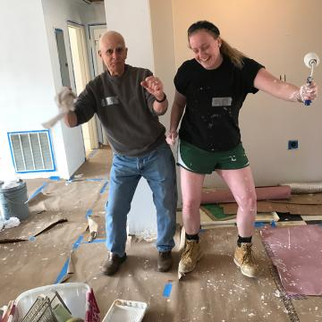 Mary Soares '19 and John, a volunteer with the Pickens County Habitat for Humanity Chapter, dancing at a worksite.