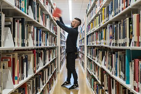 Student grabbing book in the library shelves.