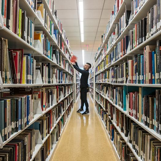 Student standing in the library stacks