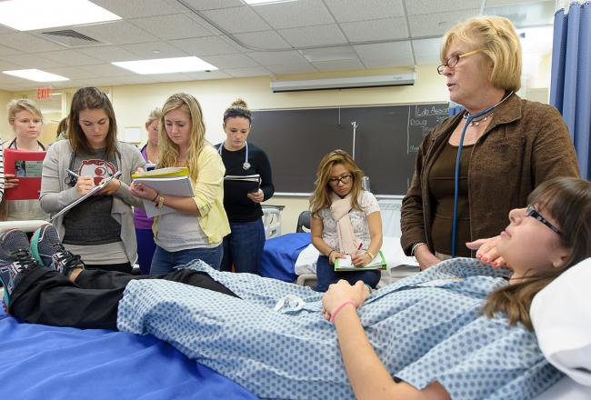 Nursing students examining a mock patient