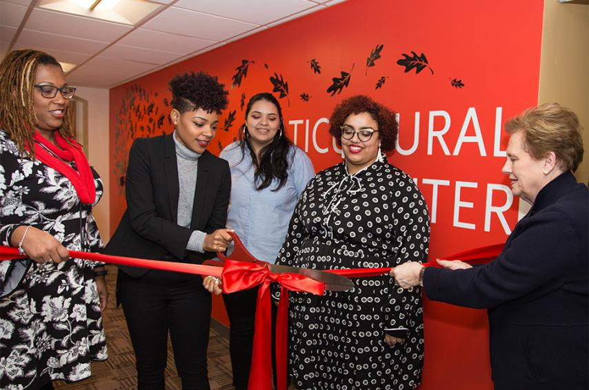 Lisa Smith-McQueenie and Helen Drinan hold ribbon as Nasyria Taylor cuts it to open the Multicultural Center