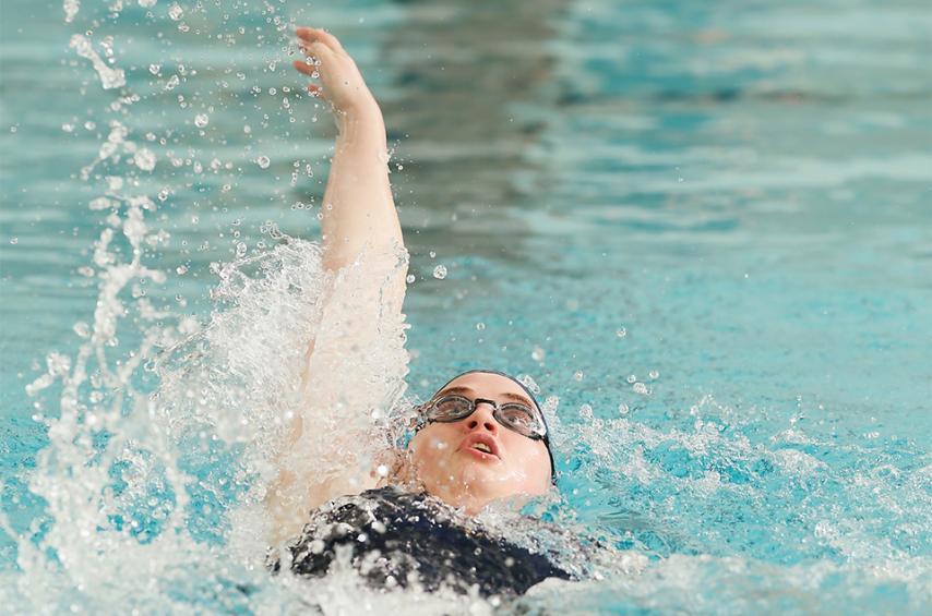 Member of the swimming and diving team doing backstroke.