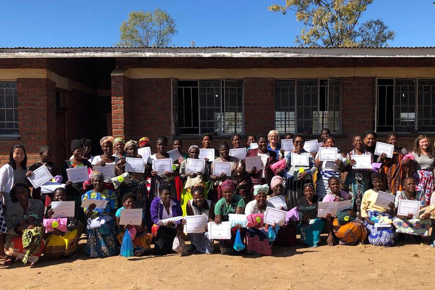 The women of Chipoka holding up their certificates, LuoPacks, and bars of soap upon completion of their women's health training!