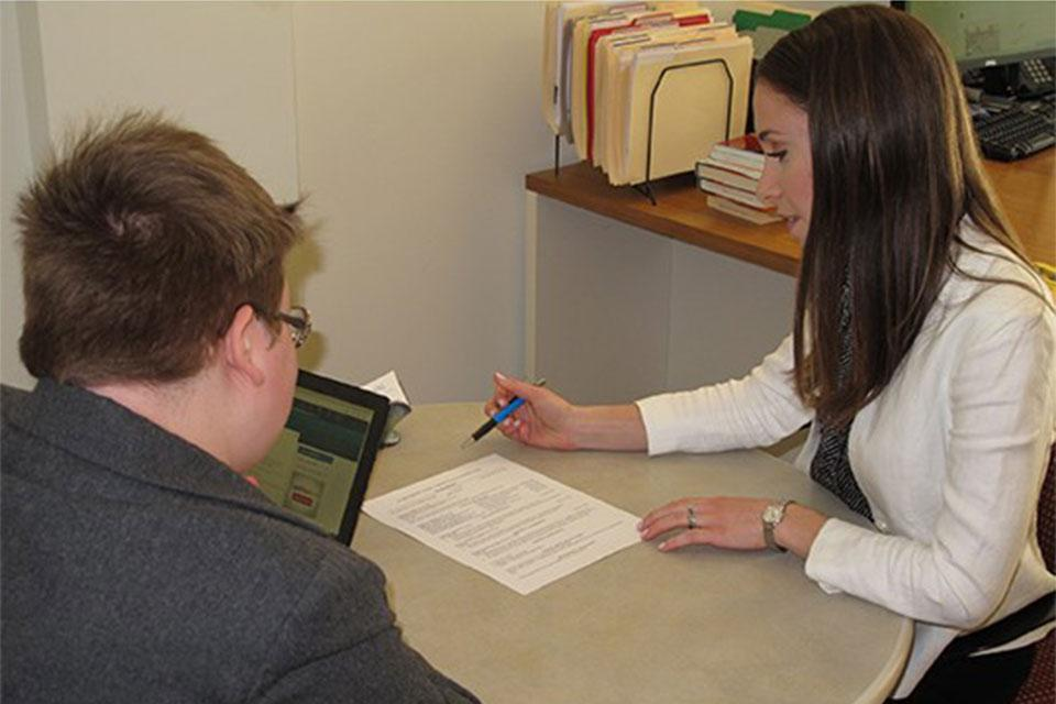 Career Education Center staff member reviewing a students resume in an office.