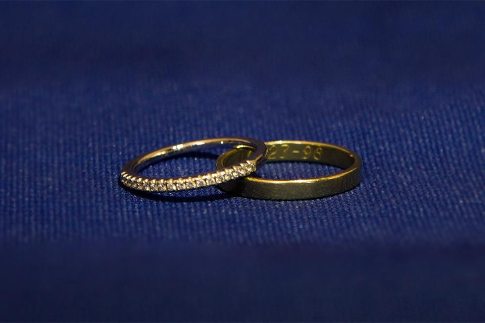 Two wedding rings on a blue background